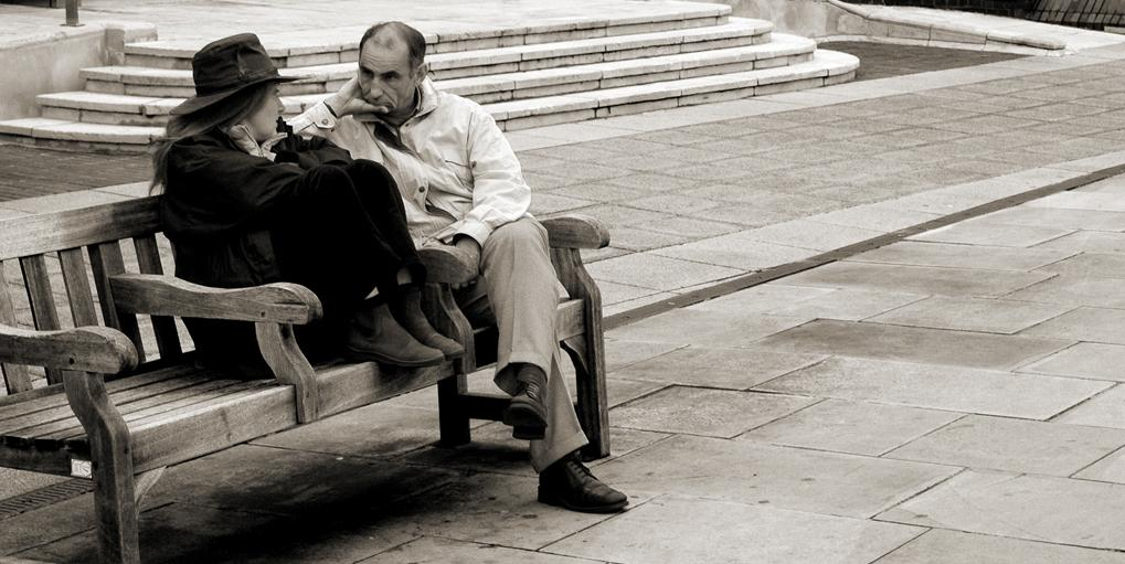 Two people sitting on a bench talking