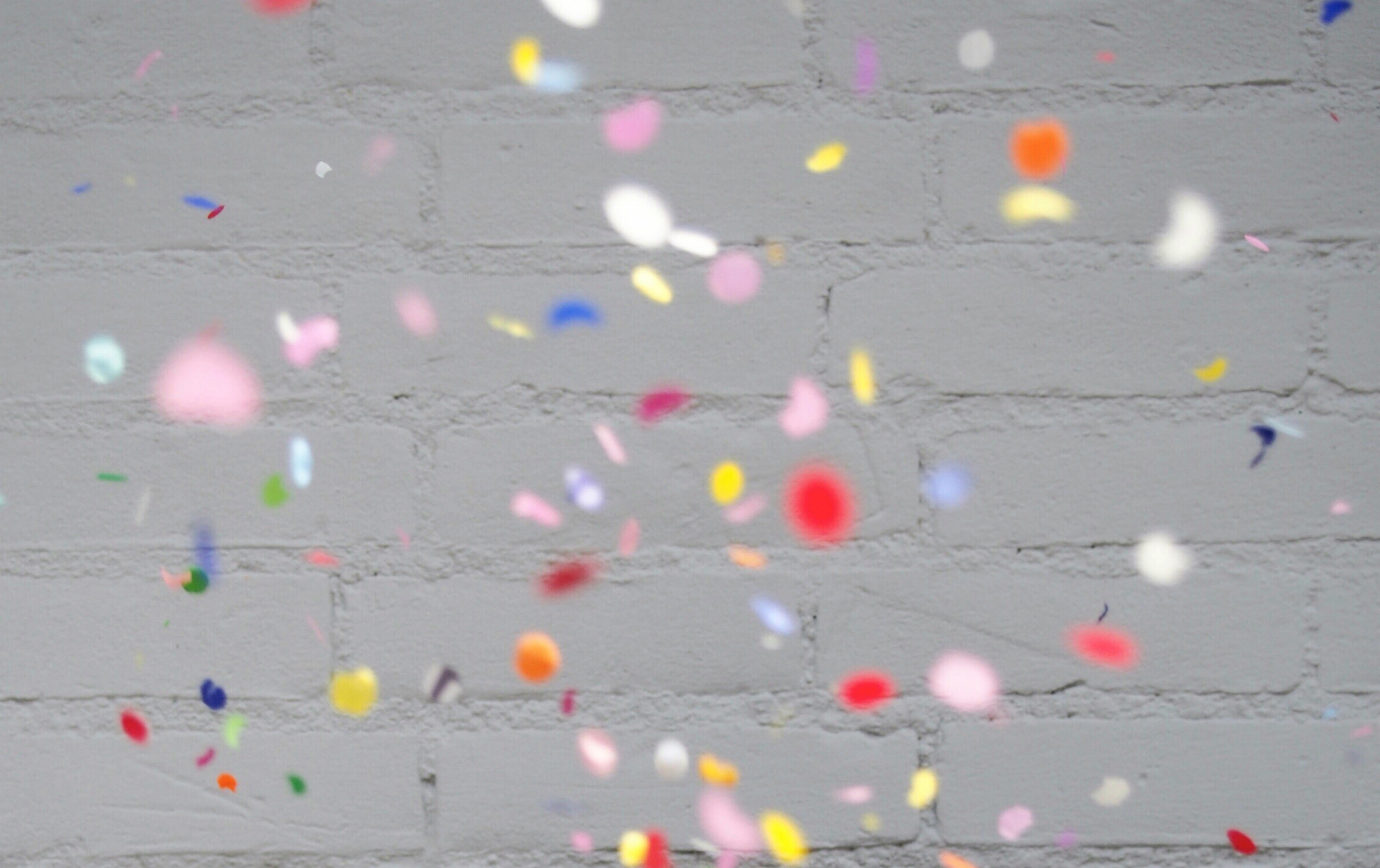 confetti against a white brick wall