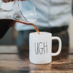 "Photo by Nathan Dumlao on Unsplash [person pouring coffee into a mug with the word ""ugh"" written on it]"