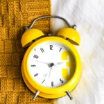 yellow clock on a knit blanket